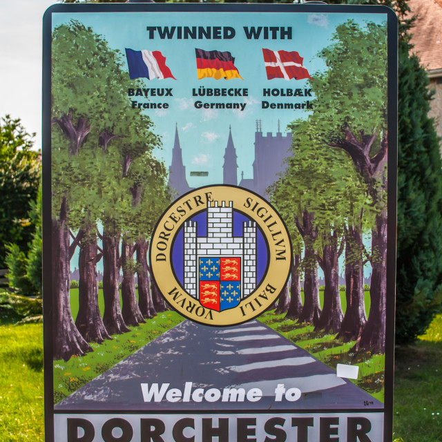 """""""Welcome to Dorset Town Sign showing twinned cities Bayeux, Lubbecke and Holbaek"""" stock image"""