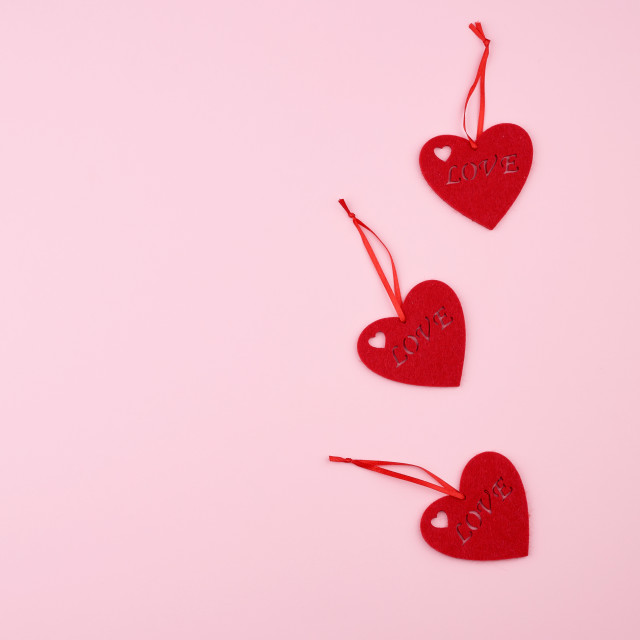 """""""three felt red hearts on a pink background."""" stock image"""