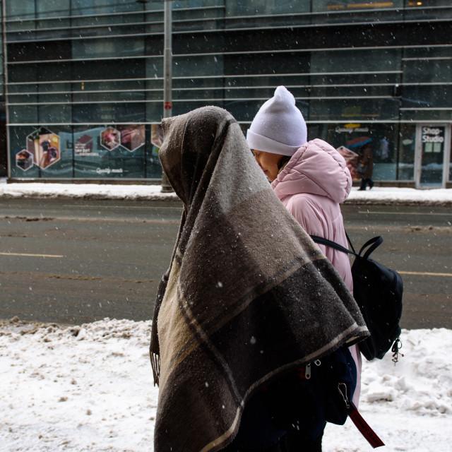 """Woman with scarf on head walks, during snowfall in Riga city. Riga, Latvia."" stock image"