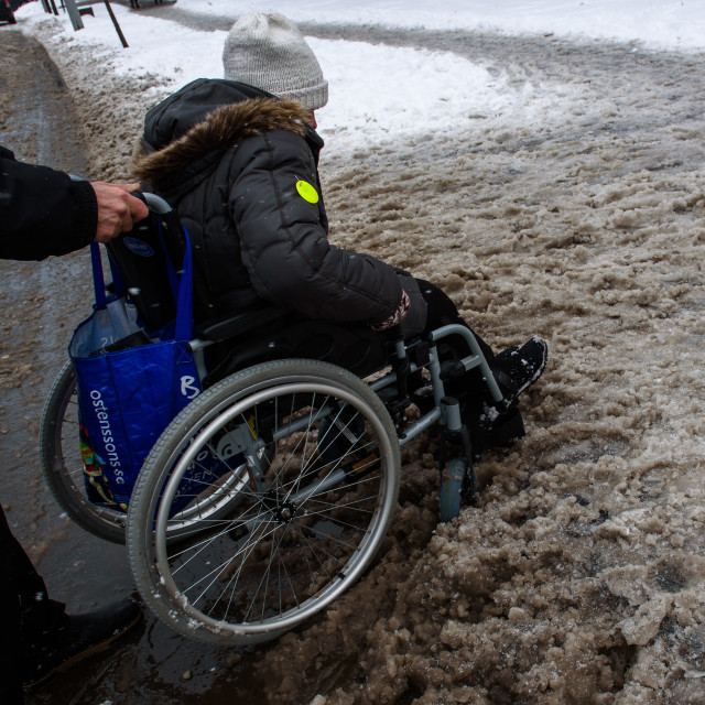 """""""Person with disabilities at wheelchair on snow covered street in Riga city. Riga, Latvia."""" stock image"""