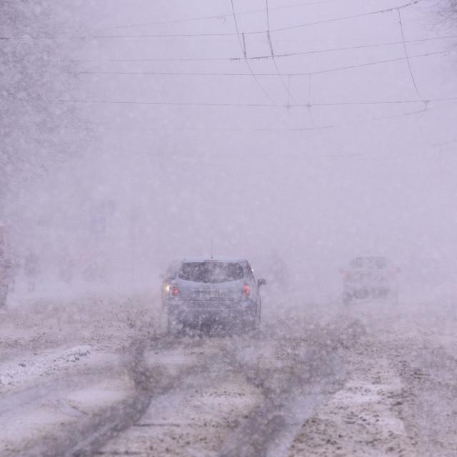 """Vehicles on the street, during Snowstorm, snowfall in Riga city. Riga, Latvia."" stock image"