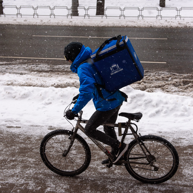 """""""Courier of Wolt company rides with bicycle, during snowfall in Riga city. Riga, Latvia."""" stock image"""