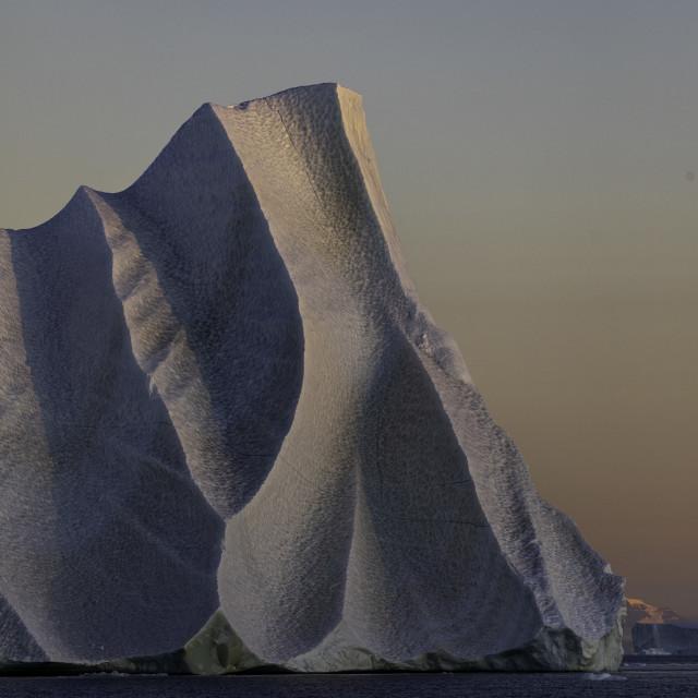 """Dramatic sunset light details a dappled iceberg"" stock image"