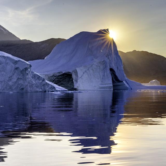 """The setting sun peaks over an iceberg"" stock image"