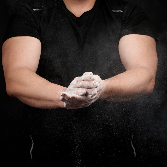 """""""muscular athlete in a black uniform rubs his hands with white dr"""" stock image"""