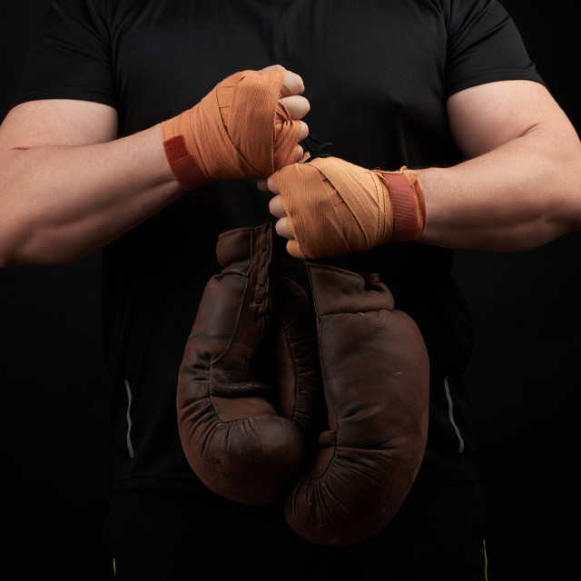"""""""muscular athlete in a black uniform holds very old brown boxing"""" stock image"""