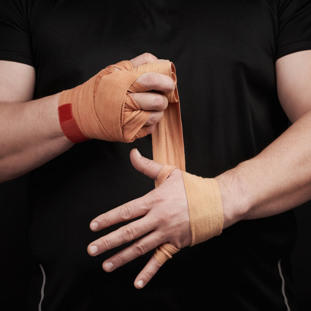 """athlete stand in black clothes and wrap his hands in red textile"" stock image"