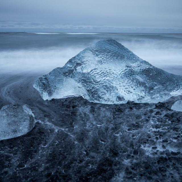 """Icebergs dot the black beach at Jokulsarlon"" stock image"