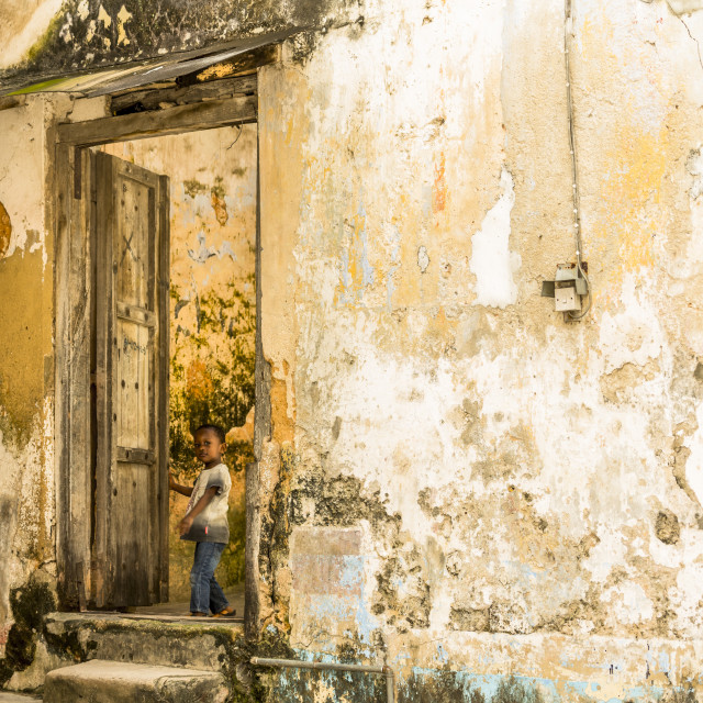 """. Child opens a doorway off an alley in Stone Town. Typica wall status throughot Stone Town."" stock image"
