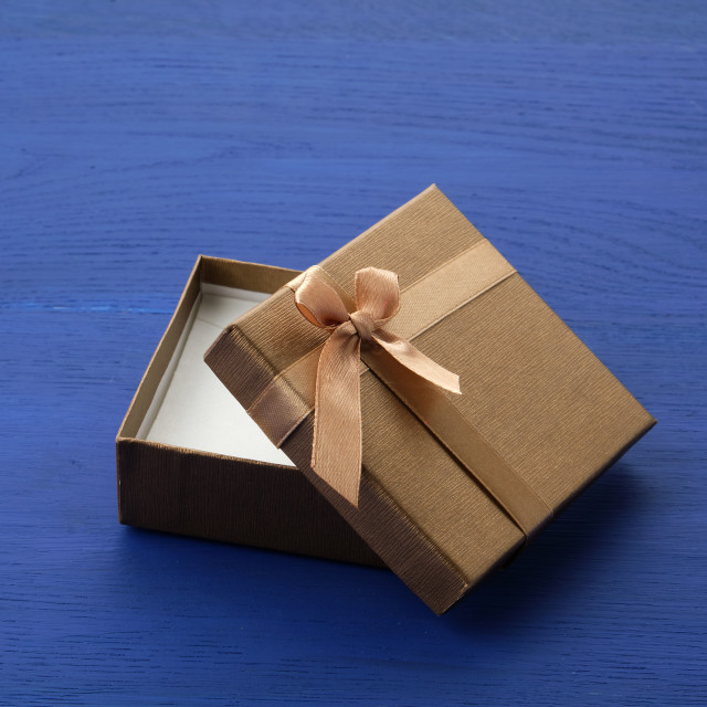 """""""open brown square cardboard empty box, item lies on a blue woode"""" stock image"""