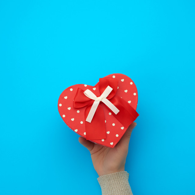 """""""female hand holding a red cardboard box with a bow on a blue bac"""" stock image"""