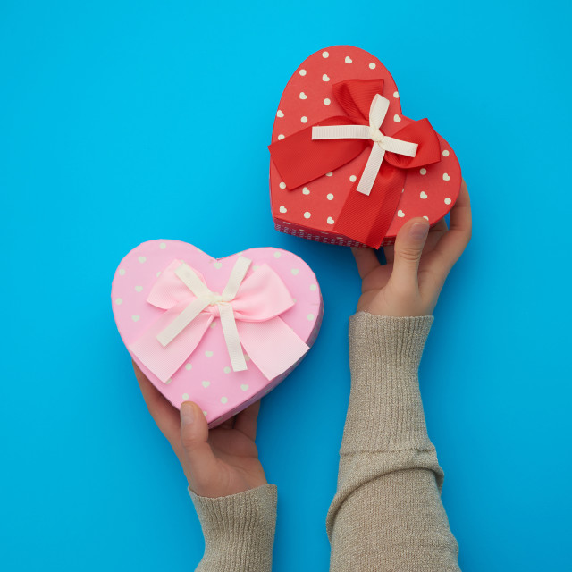 """""""female hand holding a pink cardboard box with a bow on a blue ba"""" stock image"""