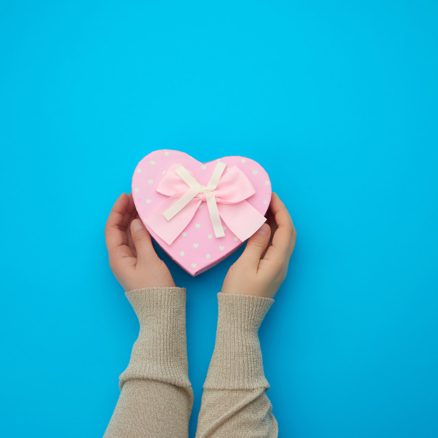 """""""female hand holding a pink cardboard box with a bow"""" stock image"""