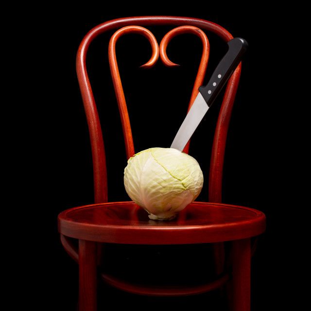 """Knife stuck on a white cabbage put on a Thonet chair"" stock image"