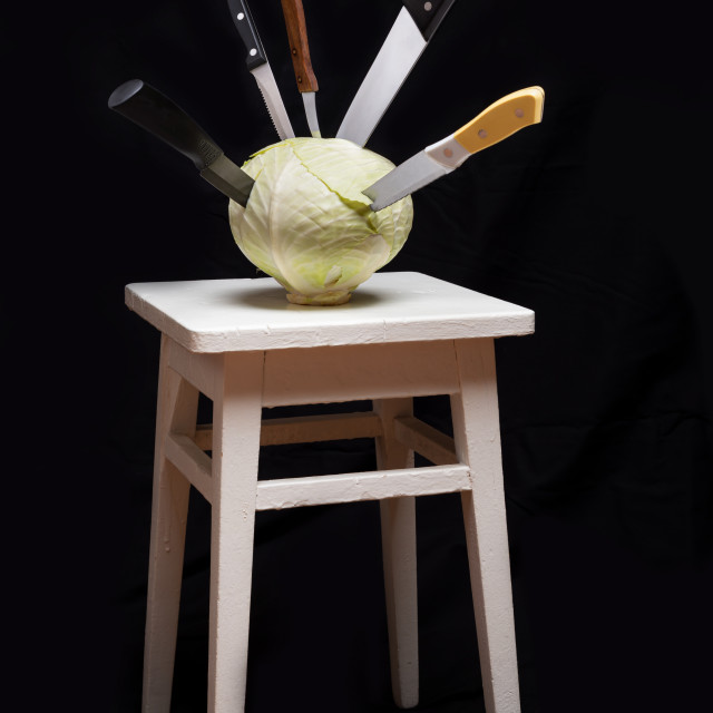 """Knives stuck on a white cabbage put on a wooden stool"" stock image"