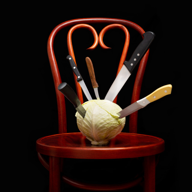 """Knives stuck on a white cabbage put on a Thonet chair"" stock image"