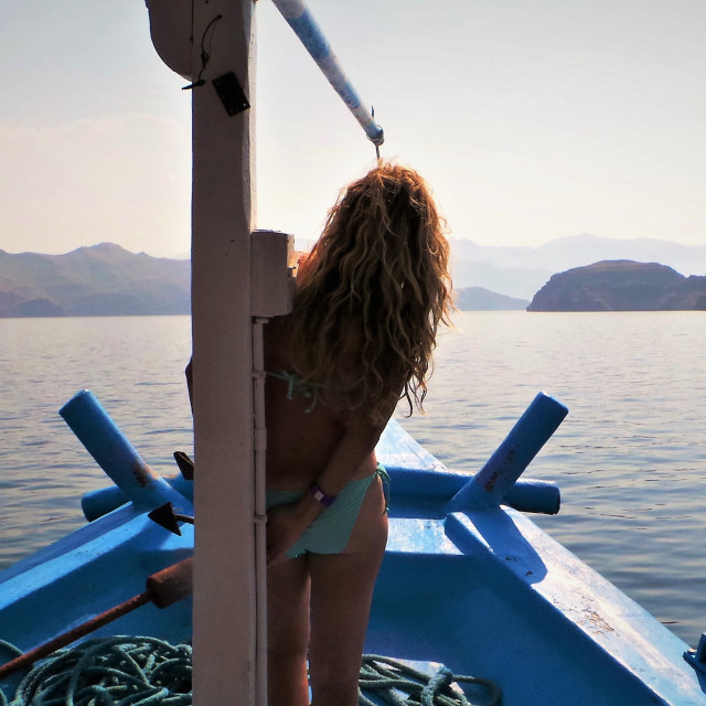 """""""Woman in bikin on an traditional dhow boat looking at the sea and scenery"""" stock image"""