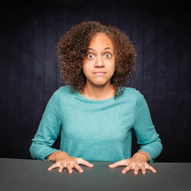 """""""Shocked Young Girl Leaning on her Hands"""" stock image"""