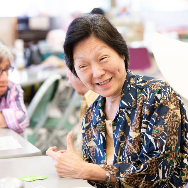 """""""Smiling Asian Woman in a Senior Activity Center"""" stock image"""
