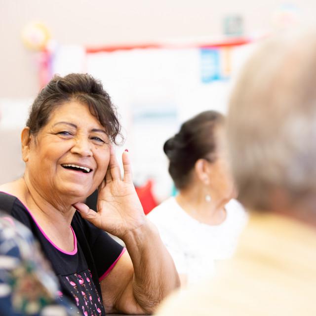 """Smiling Hispanic Woman in a Senior Activity Center"" stock image"