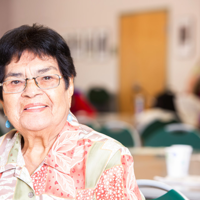 """""""Smiling Hispanic Woman in a Busy Senior Center"""" stock image"""