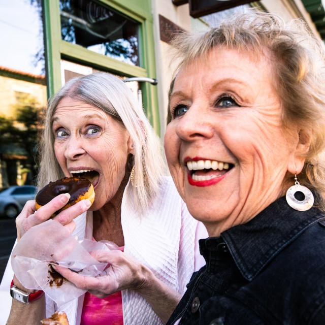 """Senior Women Eating Donuts Outdoors"" stock image"