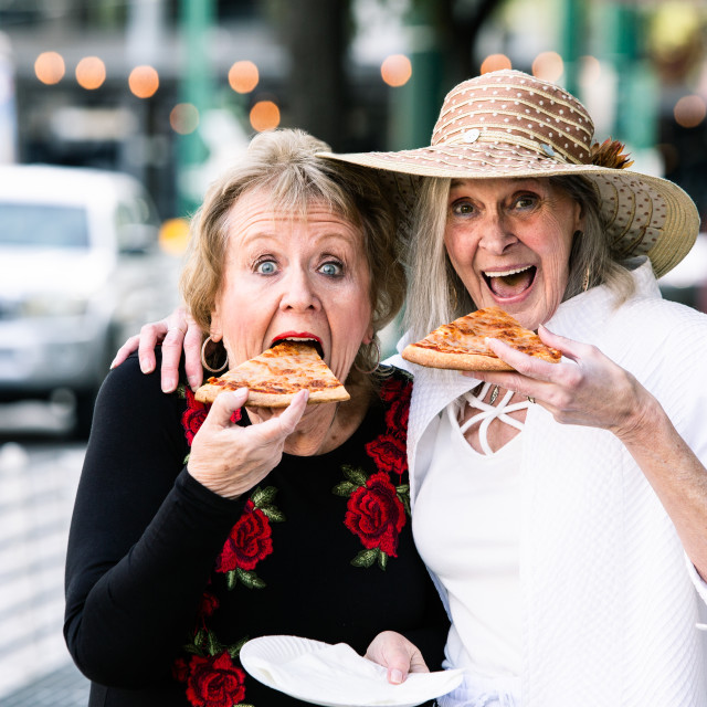 """Senior Women Taking Big Bites of Pizza"" stock image"