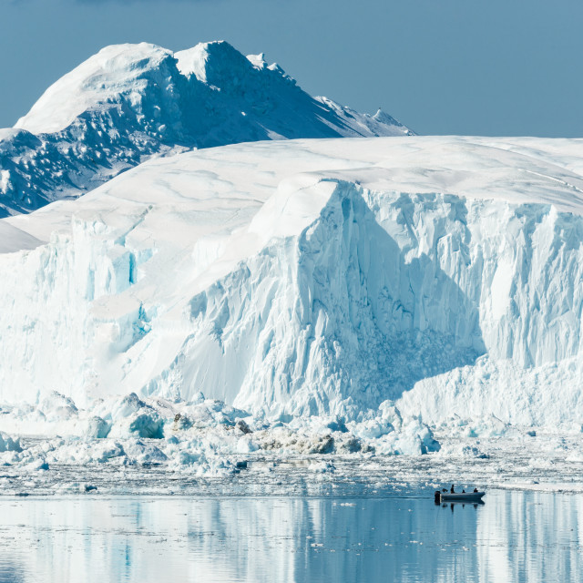 """Motorboat dwarfed by towering glacier on calm sea."" stock image"