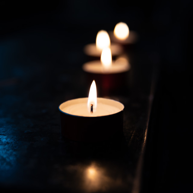 """""""Tea candles in a church resting on a dark surface reflect their"""" stock image"""