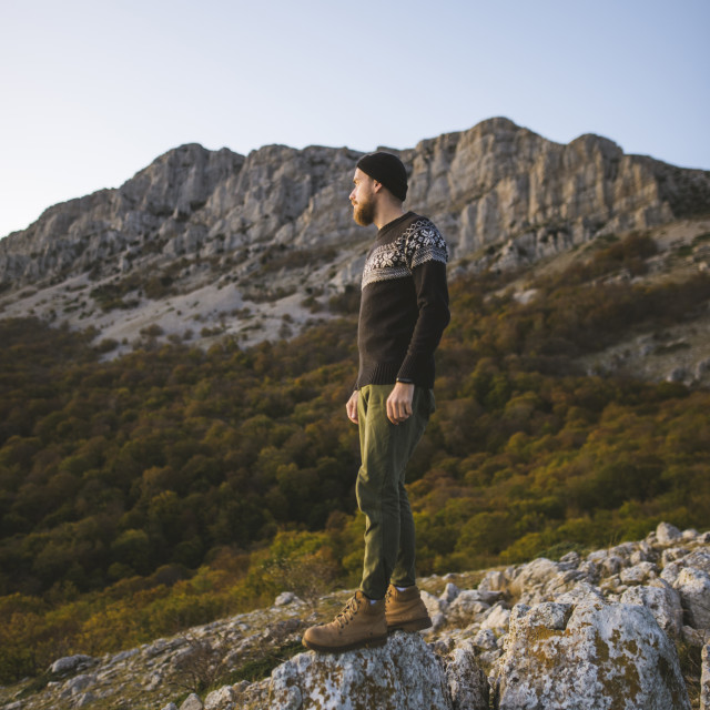 """Man standing on rock by mountain"" stock image"