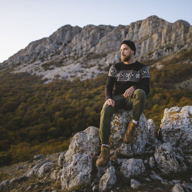 """Man sitting on rock by mountain"" stock image"