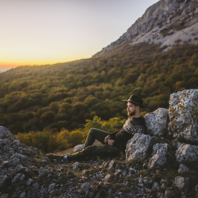 """Man lying on rock by mountain"" stock image"