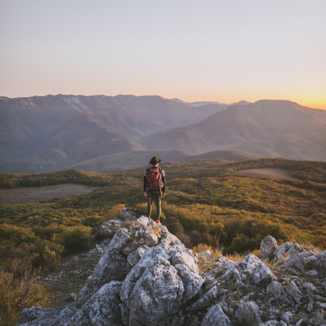 """Man on rock by mountains at sunset"" stock image"
