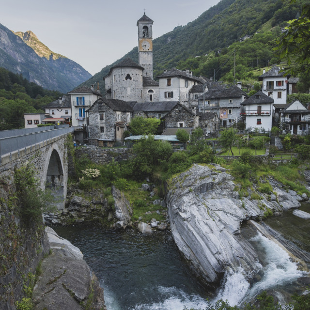 """Bell tower by bridge and river in Ticino, Switzerland"" stock image"