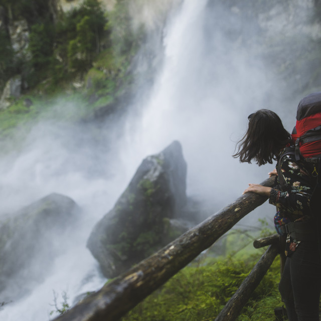 """Woman wearing backpack by waterfall"" stock image"