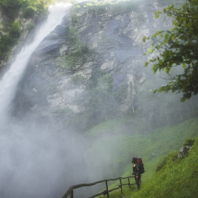 """Woman on grass by waterfall"" stock image"