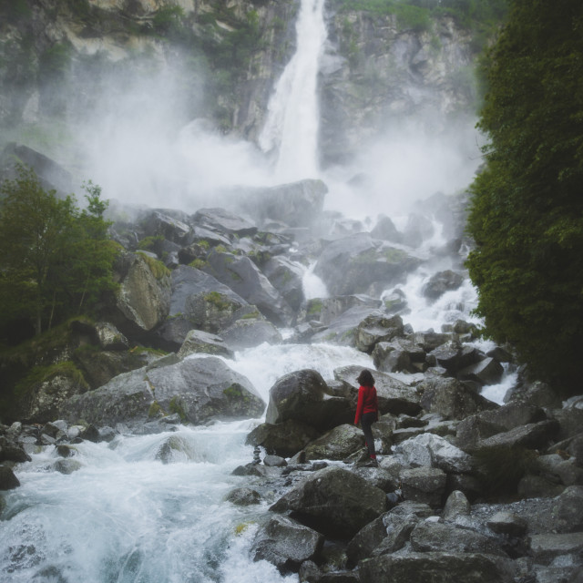 """Woman on rocks by waterfall"" stock image"
