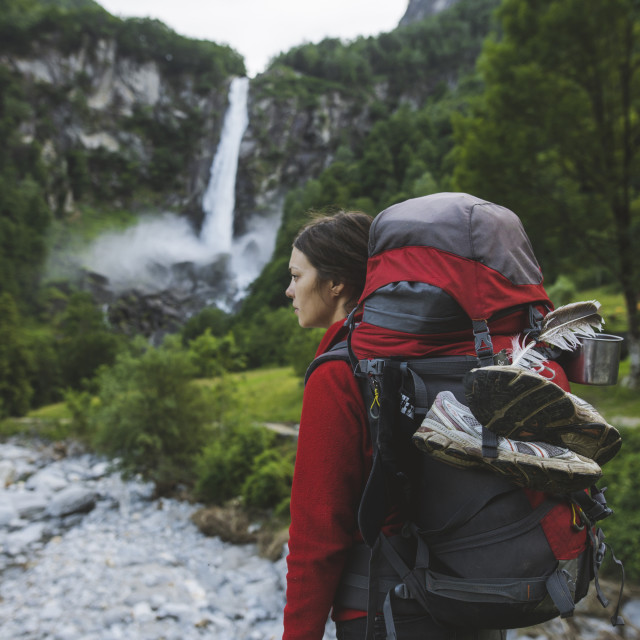"""Woman wearing backpack with waterfall in distance"" stock image"