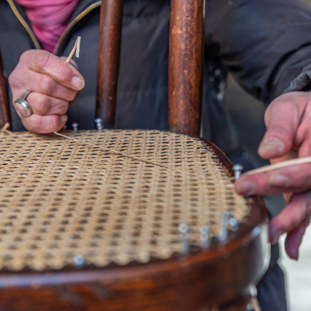 """""""The hands of an artisan weave the wooden chair"""" stock image"""