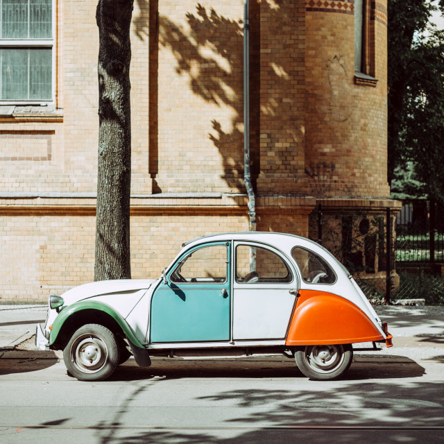 """Side view of colorful vintage car parked in street"" stock image"
