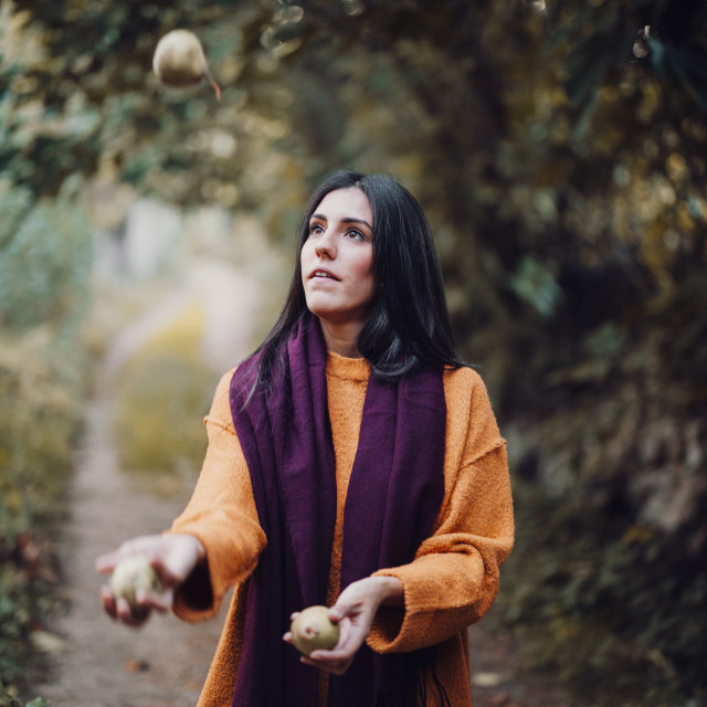 """Woman juggling some pears in the field"" stock image"