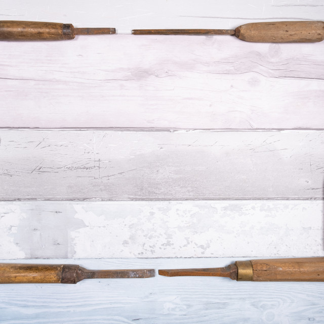 """Old wood chisels forming a frame on a background of old boards. Top view with..."" stock image"