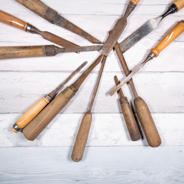 """Assortment of old wood chisels on a background of old boards. Top view"" stock image"