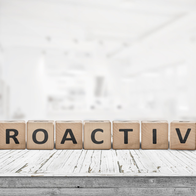 """""""Proactive sign on a wooden table in a bright office"""" stock image"""