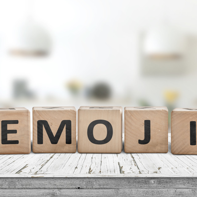 """""""The word emoji on a wooden sign in a bright room"""" stock image"""