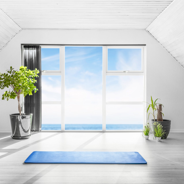 """""""Indoor yoga scene with a blue mat in a bright room"""" stock image"""