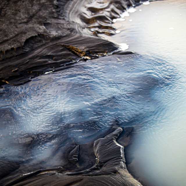 """Rippling Water over Volcanic Rock Silt in Iceland"" stock image"