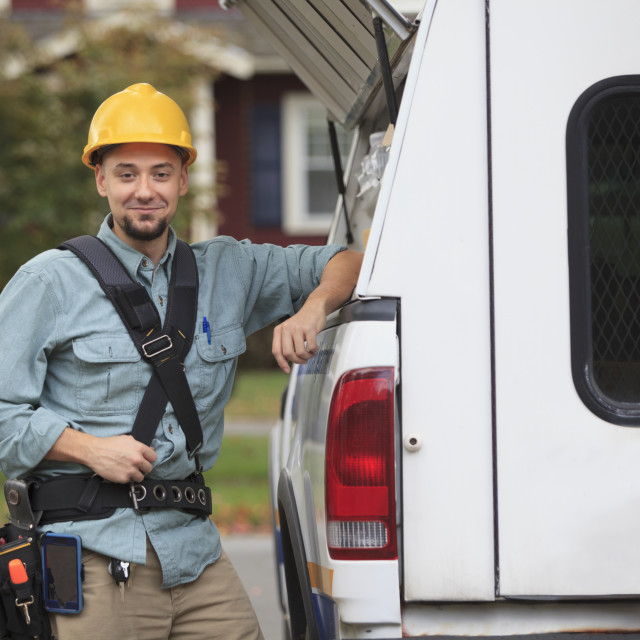 """""""Tradesman retrieving supplies from an open hatch on the side of his work truck"""" stock image"""