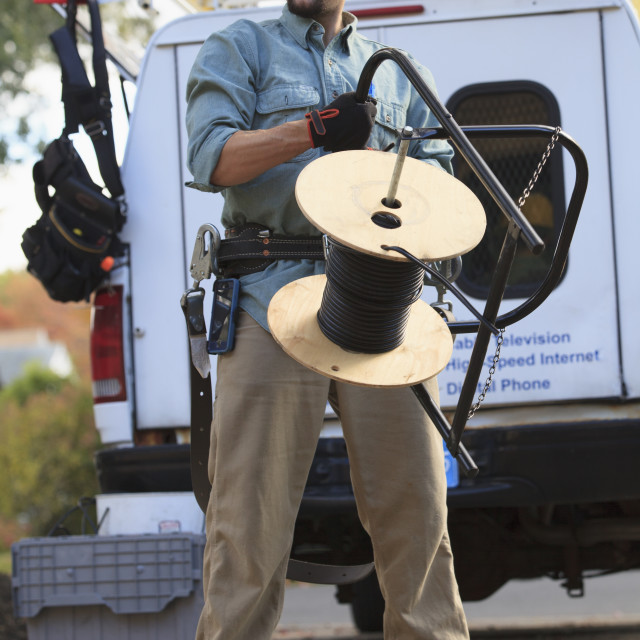"""""""Tradesman holding cable for internet installation with work truck behind him"""" stock image"""