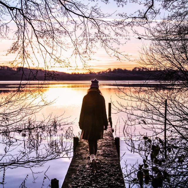 """""""Woman walking towards the sunrise"""" stock image"""